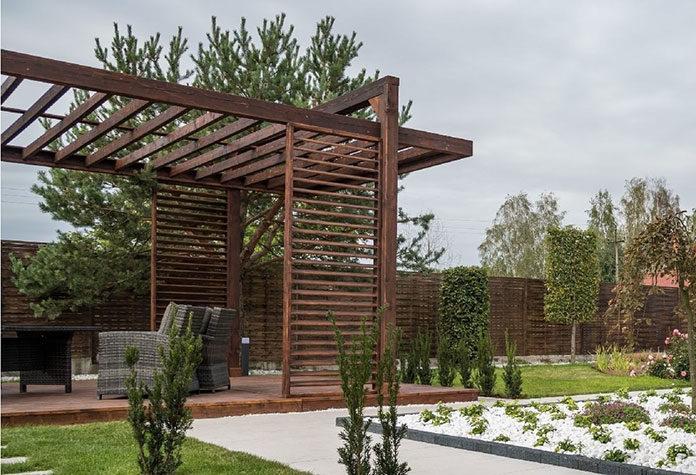 Pergola w ogrodzie – dwa pomysły na typowe zaaranżowanie zieleni z drewnianą pergolą w tle